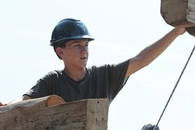 boy in hard hat raises arm to lift piece of wood